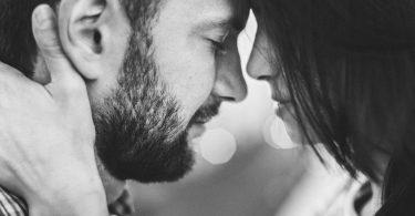 Homem e mulher brancos com as testas encostadas.