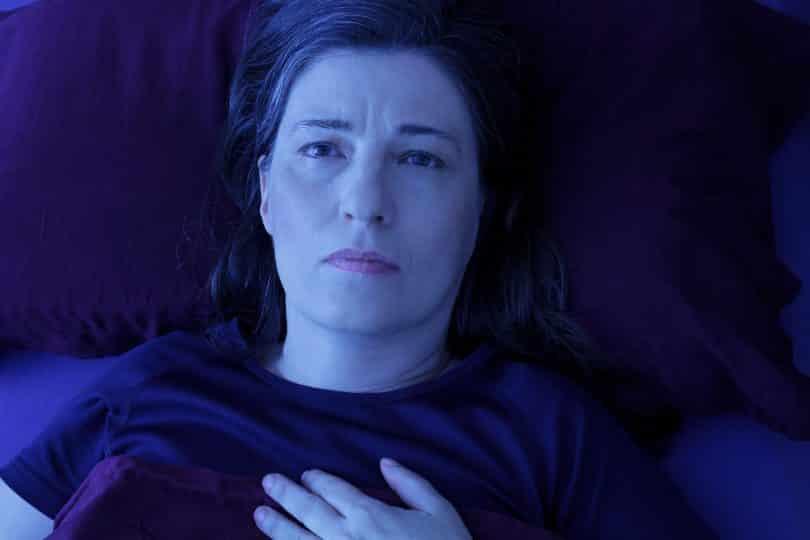Mulher com expressão facial preocupada. Ela está deitada em uma cama.