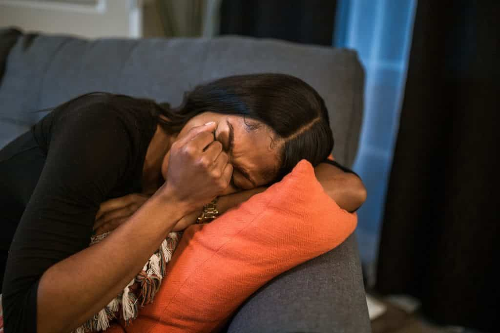Mulher deitada com a mão no rosto com expressão de tristeza