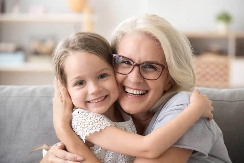 Avó e neta criança se abraçam e sorriem.
