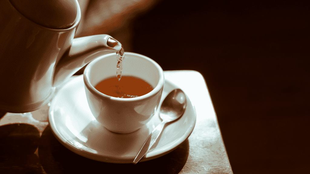 Bule colocando chá quente em xícara