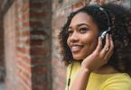 Mulher sorridente escutando algo no fone de ouvido