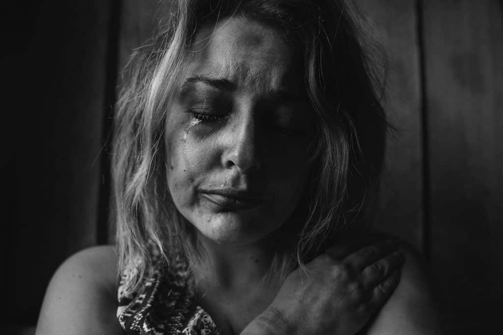Mulher chorando, com maquiagem borrada em seu rosto, e hematomas.