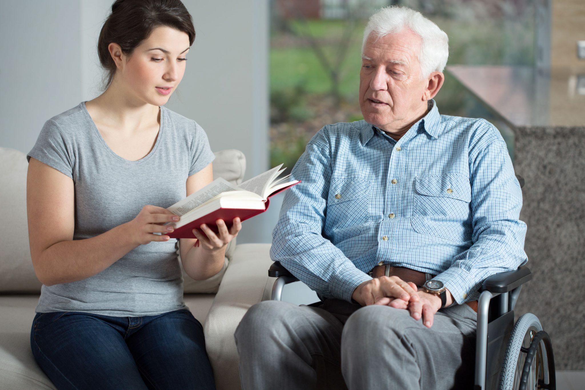 Mulher lendo para o senhor ao seu lado de cadeira de rodas