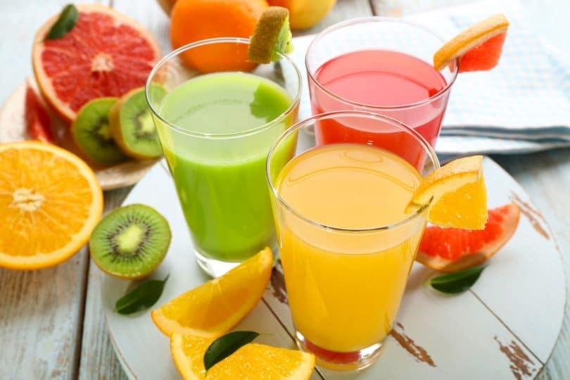 Três copos sobre uma mesa cheios de diferentes tipos de sucos naturais. Ao redor, várias frutas estão dispostas cortadas ao meio.