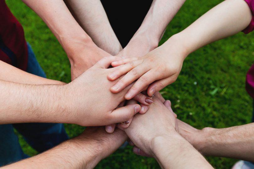 Mãos unidas de outras pessoas no centro