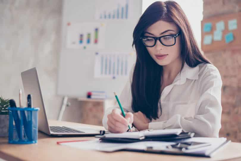 Mulher branca de óculos sentada em frente à uma mesa de escritório escrevendo num caderno.