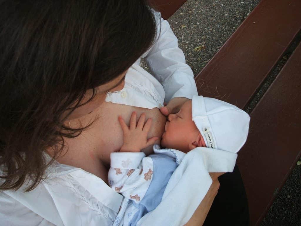 Mulher vista de cima amamentando seu bebê recém-nascido.