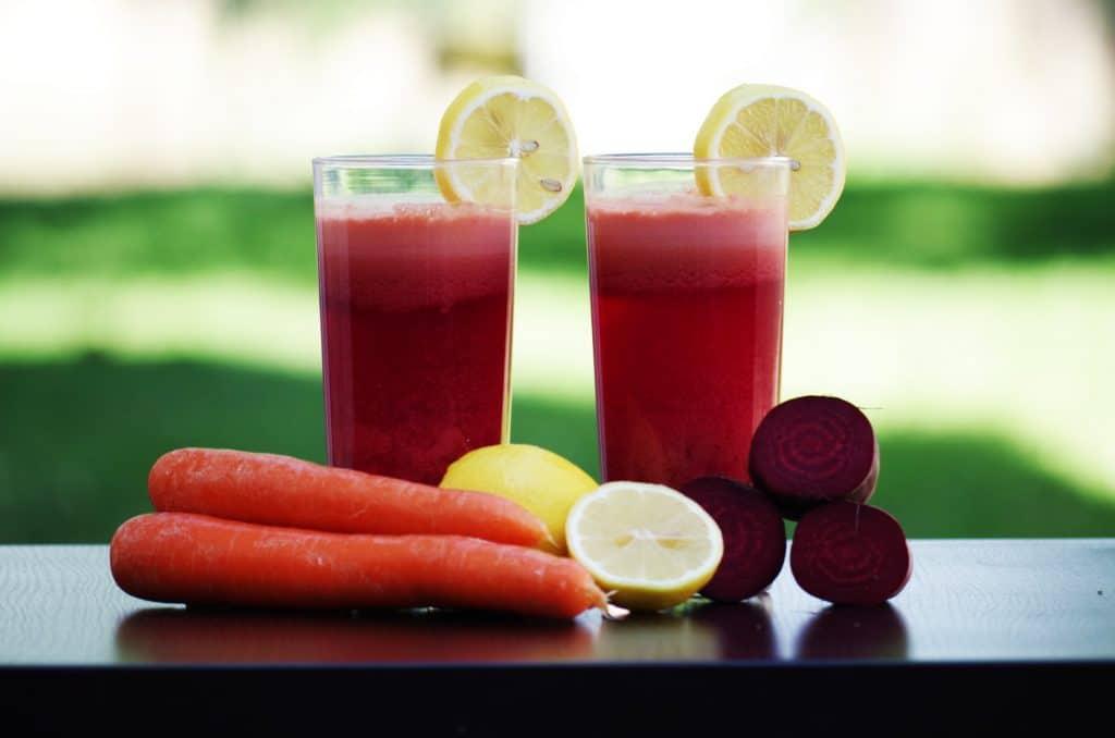 Dois copos de suco de limão, laranja e beterraba ao lado dos ingredientes.