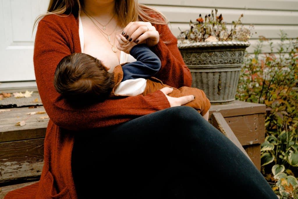 Mulher sentada no quintal durante o dia amamentando seu bebê.