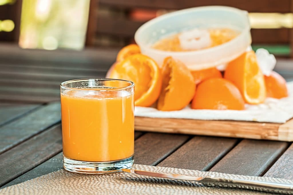 Suco de laranja sobre uma mesa de madeira, com as cascas das frutas atrás.