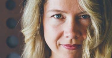 Close em rosto de mulher branca, loira e de olhos azuis.