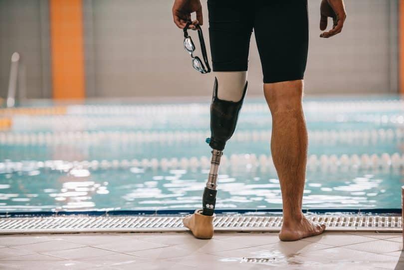 Homem à beira de piscina. Ele tem uma perna protética.