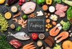 Carne de frango, peixe, frutos do mar, vegetais e frutas e palavras Fodmap no centro, em fundo escuro.