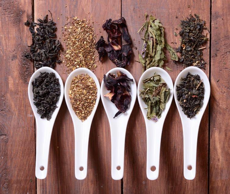Colheres brancas em cima de uma mesa de madeira. Cada colher contém uma erva diferente para chá.