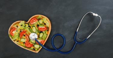 Imagem de uma vasilha em formato de coração cheia de salada. Ao lado, um estetoscópio.