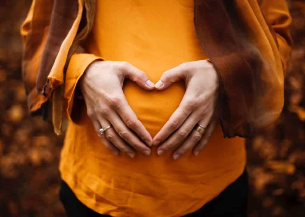 Mulher grávida vista de frente com as mãos sobre sua barriga.