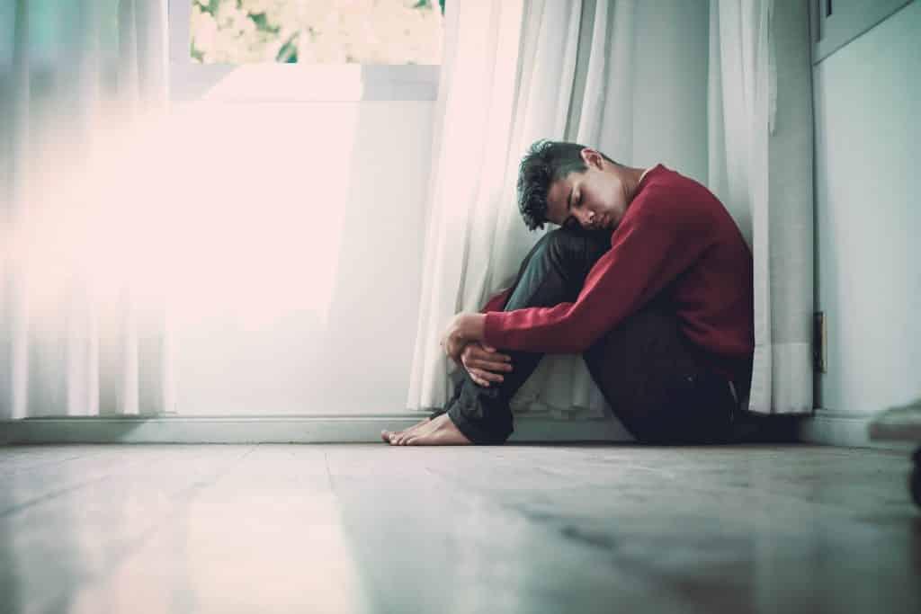 Homem sentado no chão de olhos fechados abraçando suas pernas