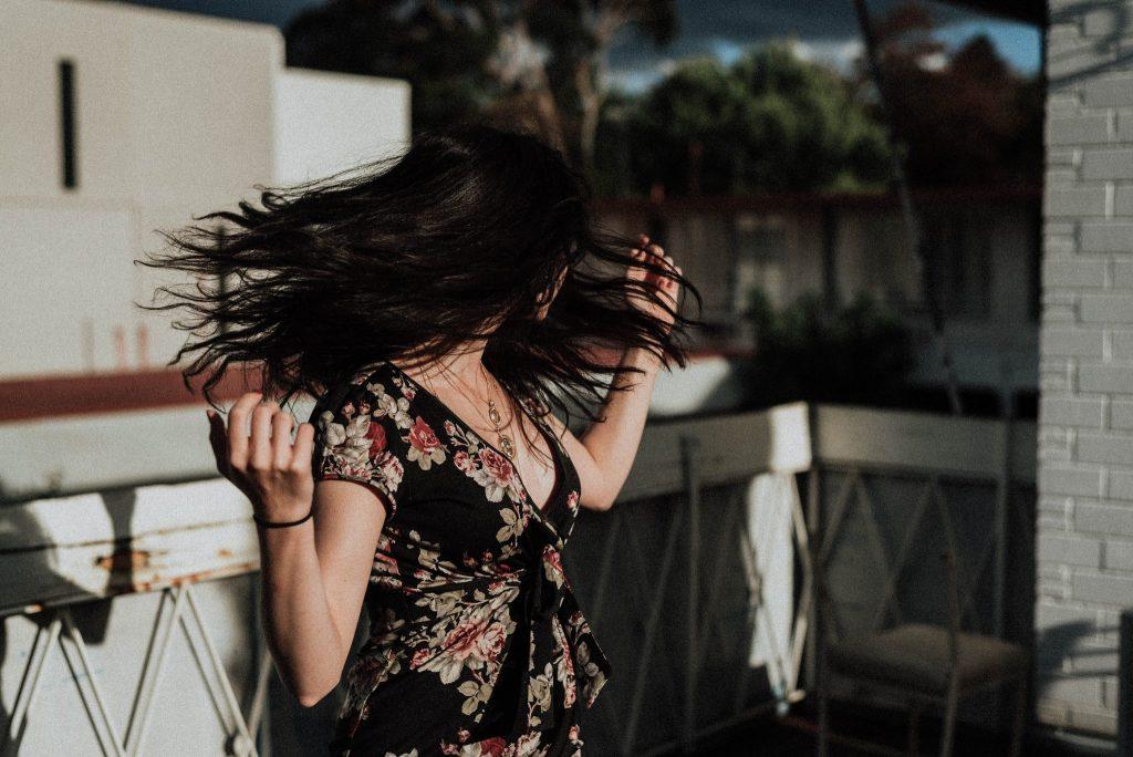 Mulher com cabelos pretos esvoaçantes.