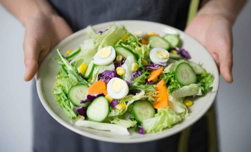 Recorte de uma pessoa segurando um prato de salada.