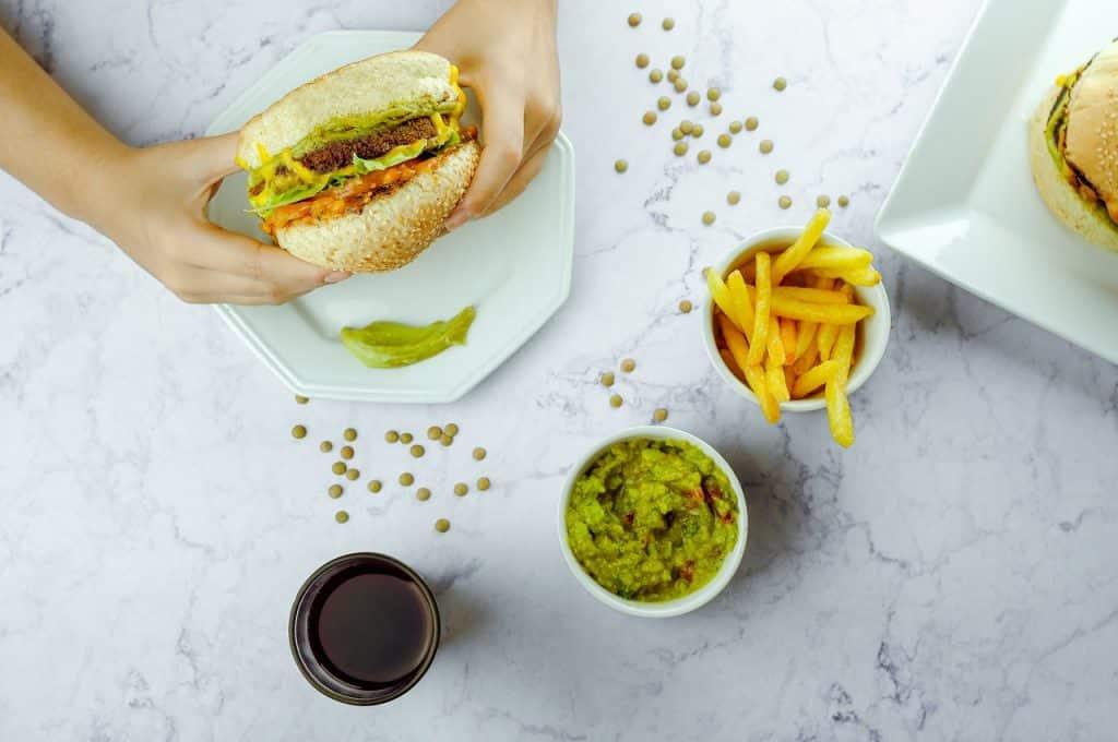 Recorte de uma pessoa segurando um lanche de hambúrguer com aperitivos em volta da mesa.