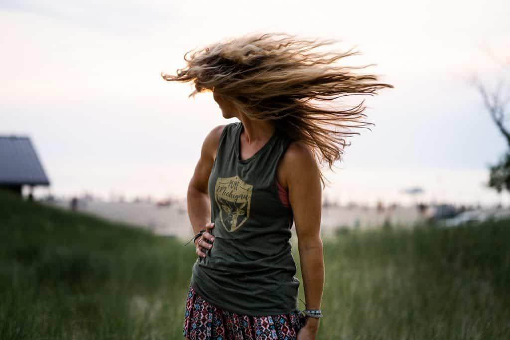 Mulher jogando os cabelos de um lado para o outro ao ar livre.