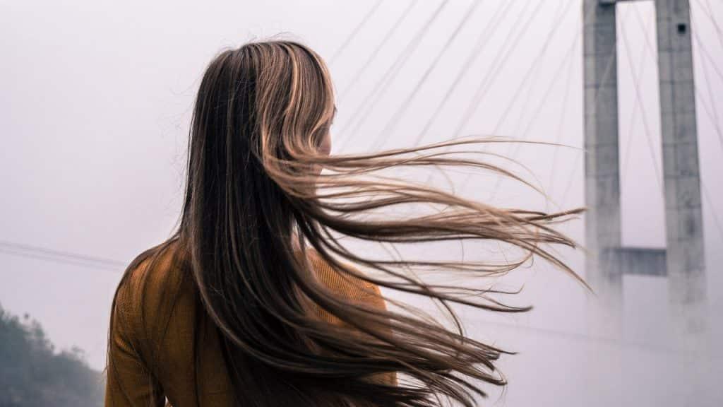 Mulher de costas com os cabelos compridos ao vento.