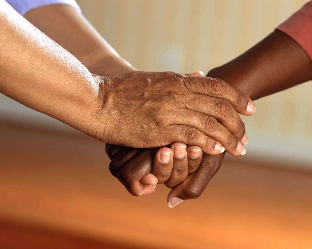 Pessoa segurando mão de outra pessoa