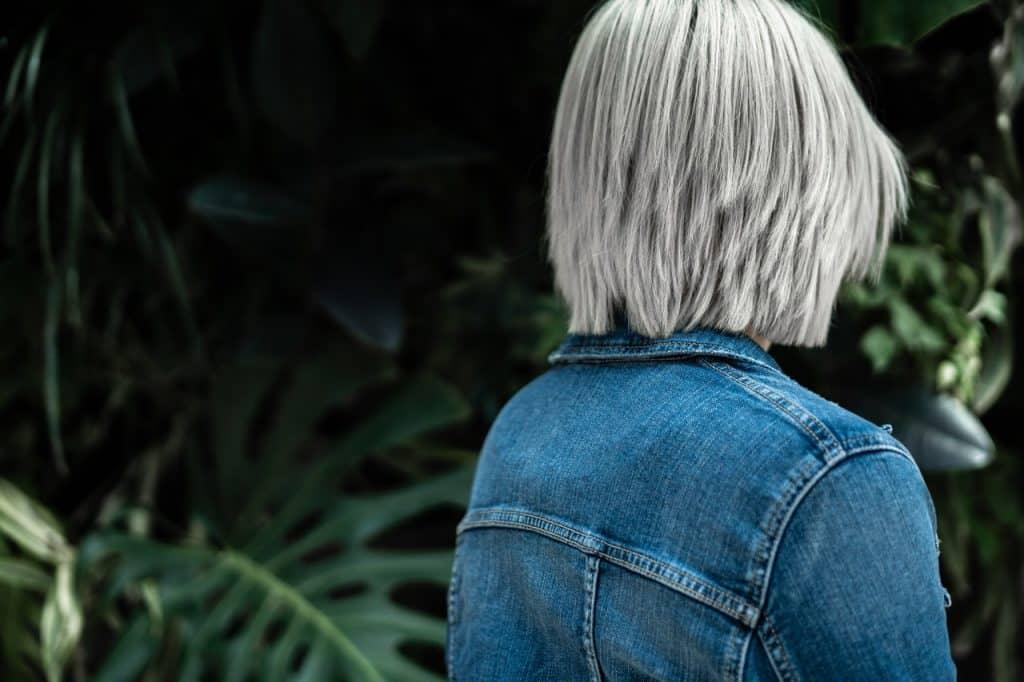 Mulher de costas para a câmera com o cabelo descolorido.