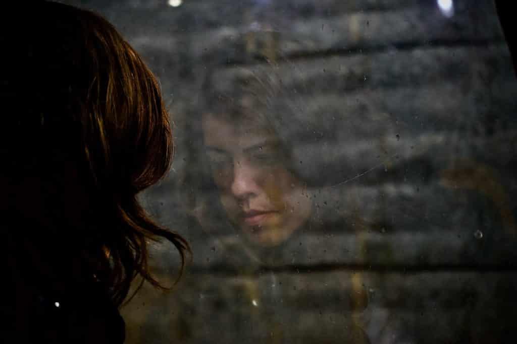 Mulher olhando para baixo com seu reflexo na janela em sua frente