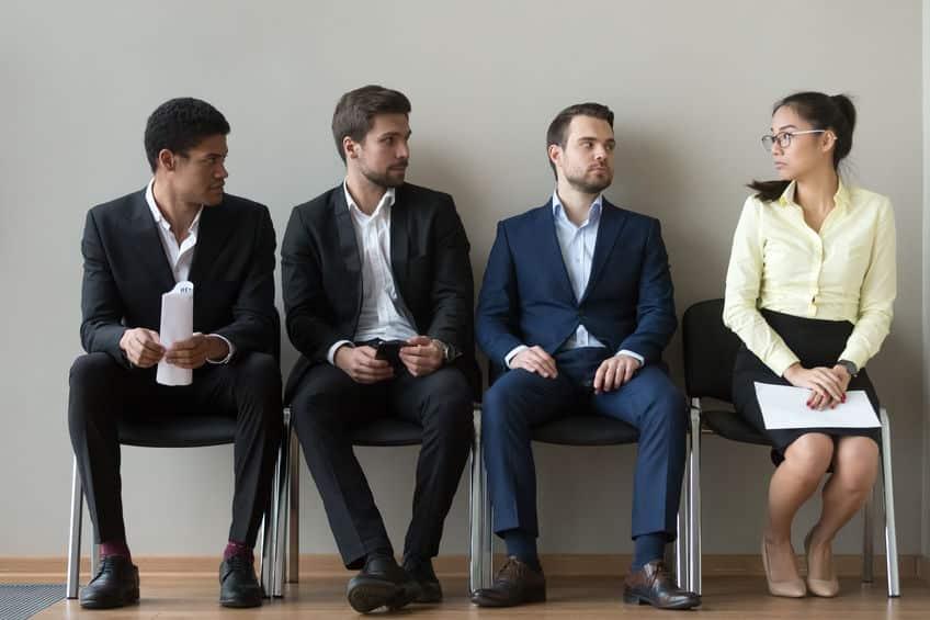 Três homens de roupas sociais sentados lado a lado, olhando para uma mulher de roupas sociais sentada ao lado.