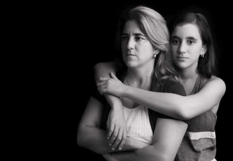 Mãe com expressão séria, de braços cruzados, enquanto sua filha a abraça.
