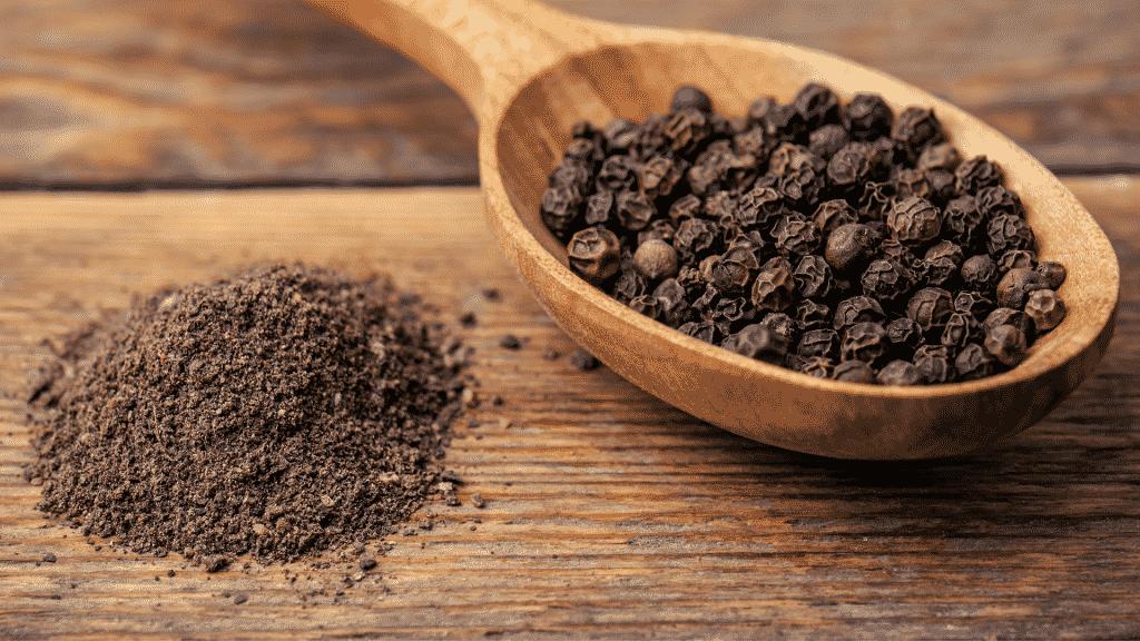 Colher de pau com sementes de pimenta-do-reino