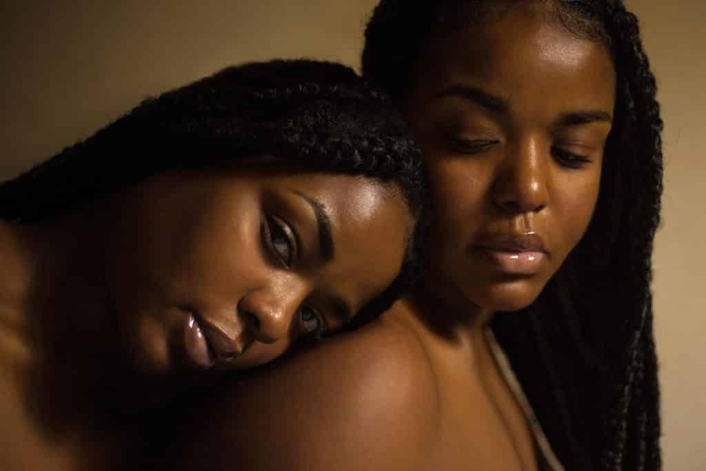 Duas mulheres abraçadas, com expressões serenas.