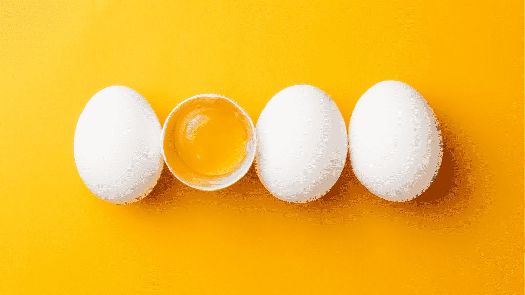 Quatro ovos no fundo amarelo com um aberto