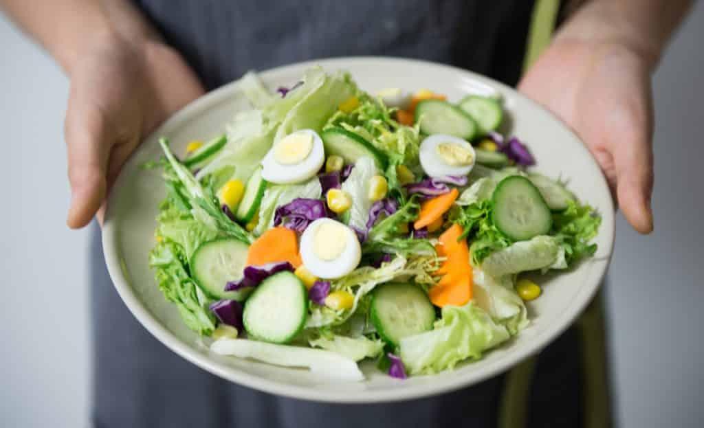Mulher segurando um prato com saladas, pepinos e ovos