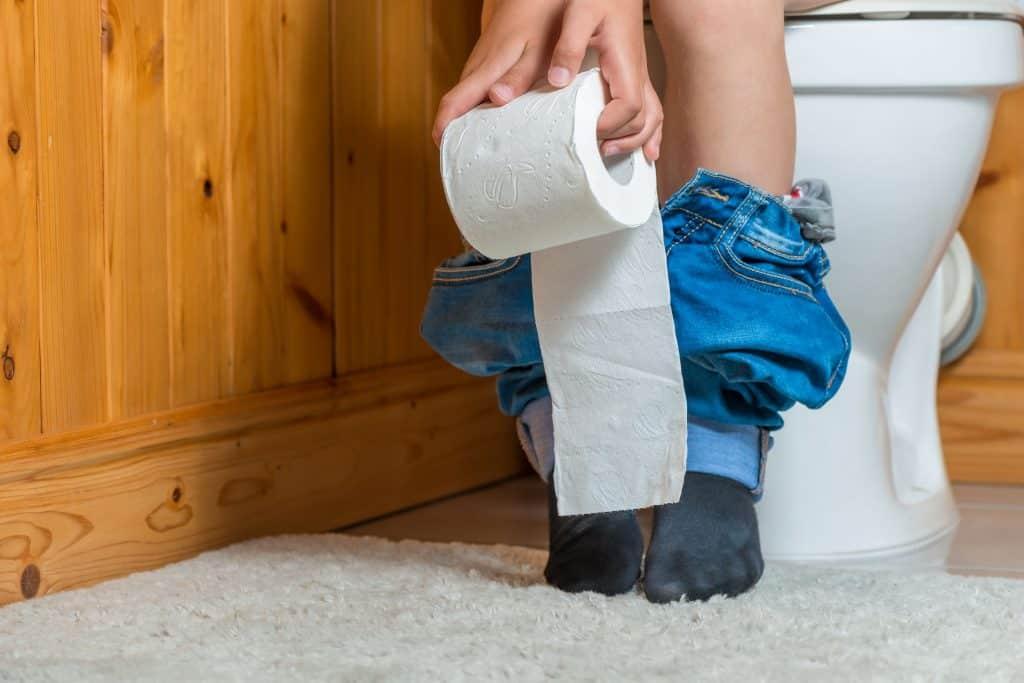 Pessoa sentada no vaso sanitário segurando papel higiênico
