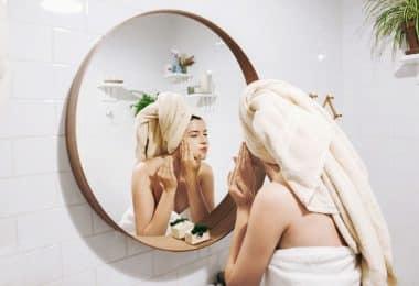 Mulher se olhando no espelho com toalha na cabeça