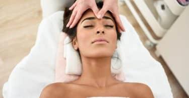 Mulher negra recebendo massagem na testa.