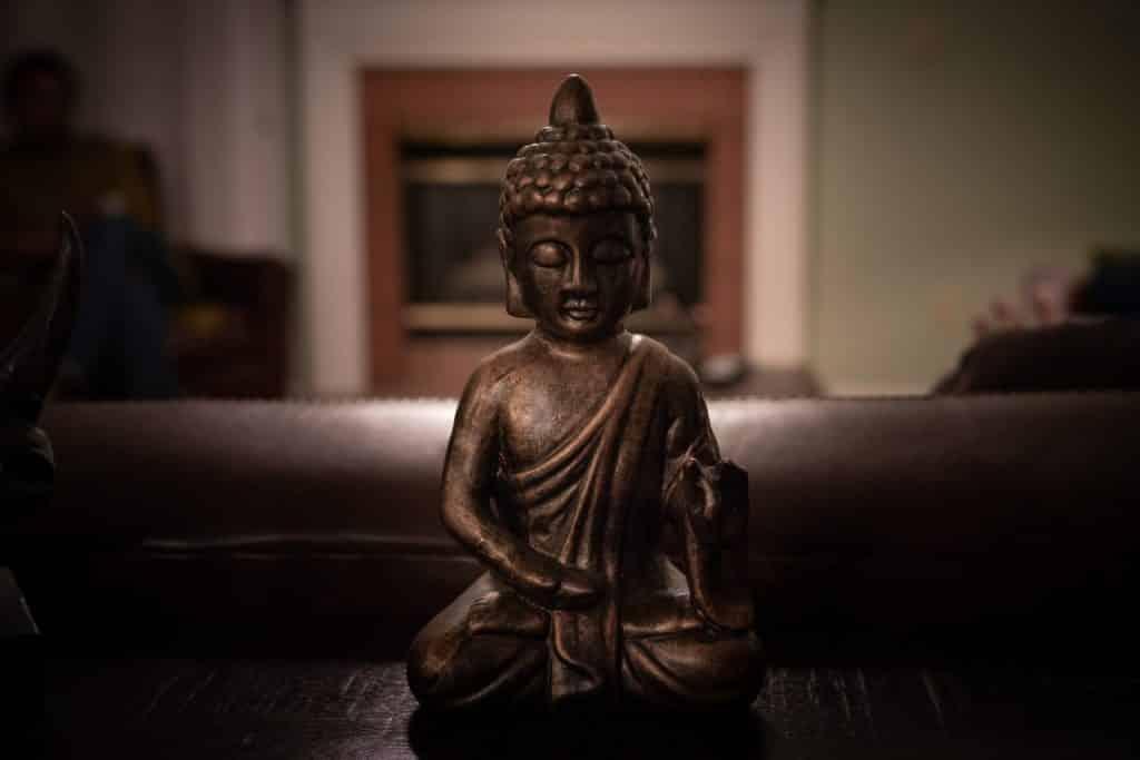 Pequena estátua de Buda em bronze, em cima de uma superfície de madeira.