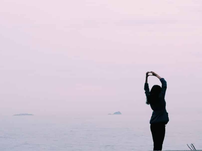 Silhueta de uma mulher em pé fazendo coração com a mão.