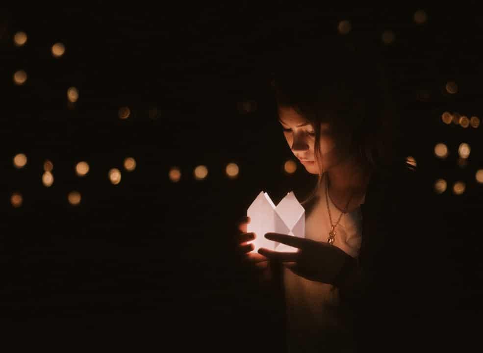 Menina segurando uma caixinha de papel com uma luz dentro.