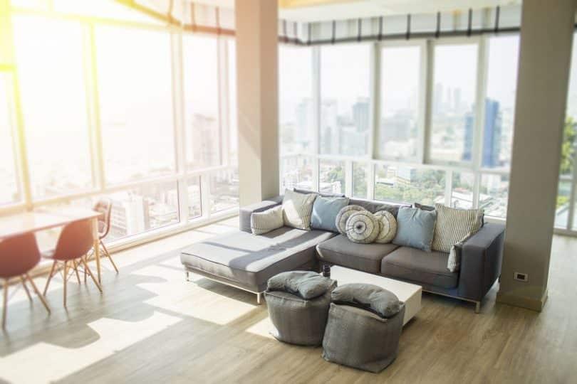 Sala de estar de um apartamento arejado com paredes de vidro.