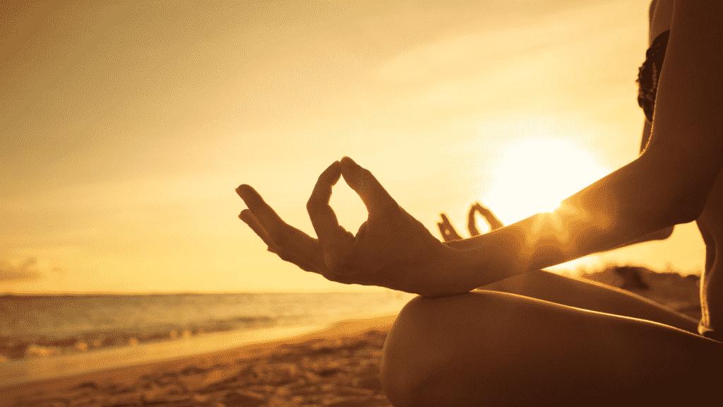 Pessoa meditando sob o pôr do sol