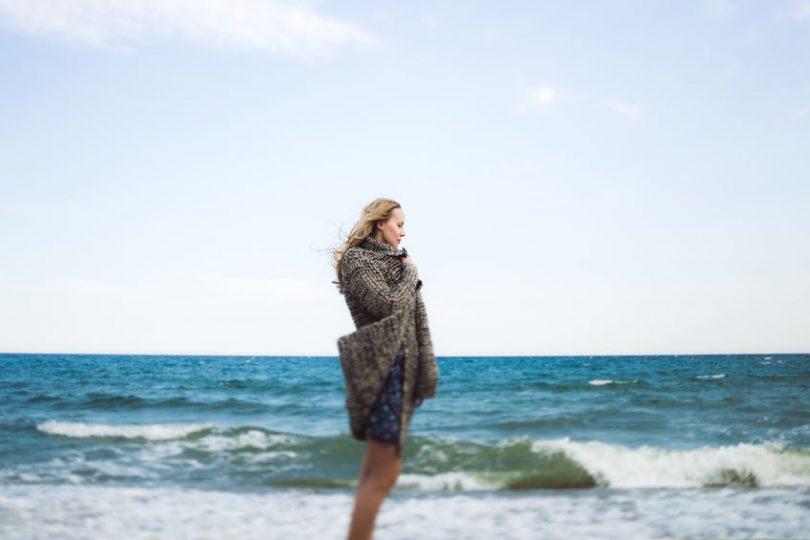 Mulher de perfil, em pé, em frente ao mar na praia.