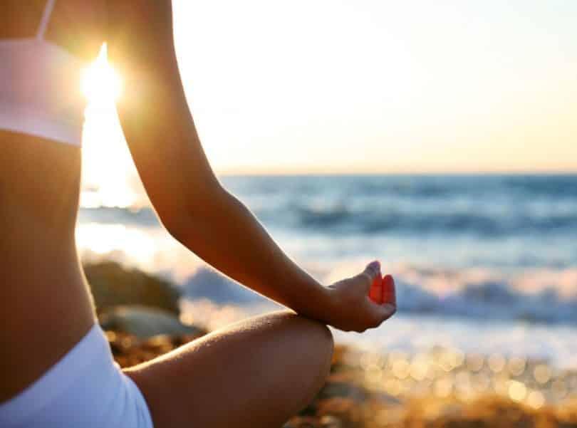 Mulher medita sobre areia da praia.