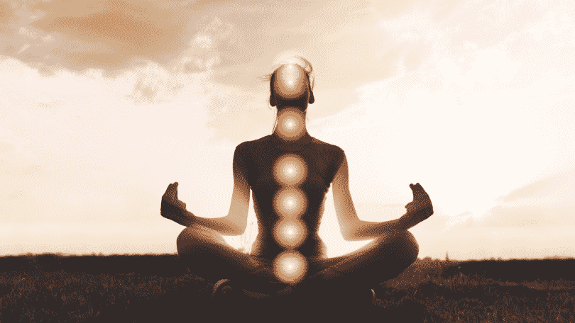 Silhueta de uma pessoa praticando Ioga e seus chakras em evidência