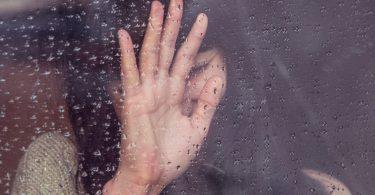 Menina com a mão na janela.