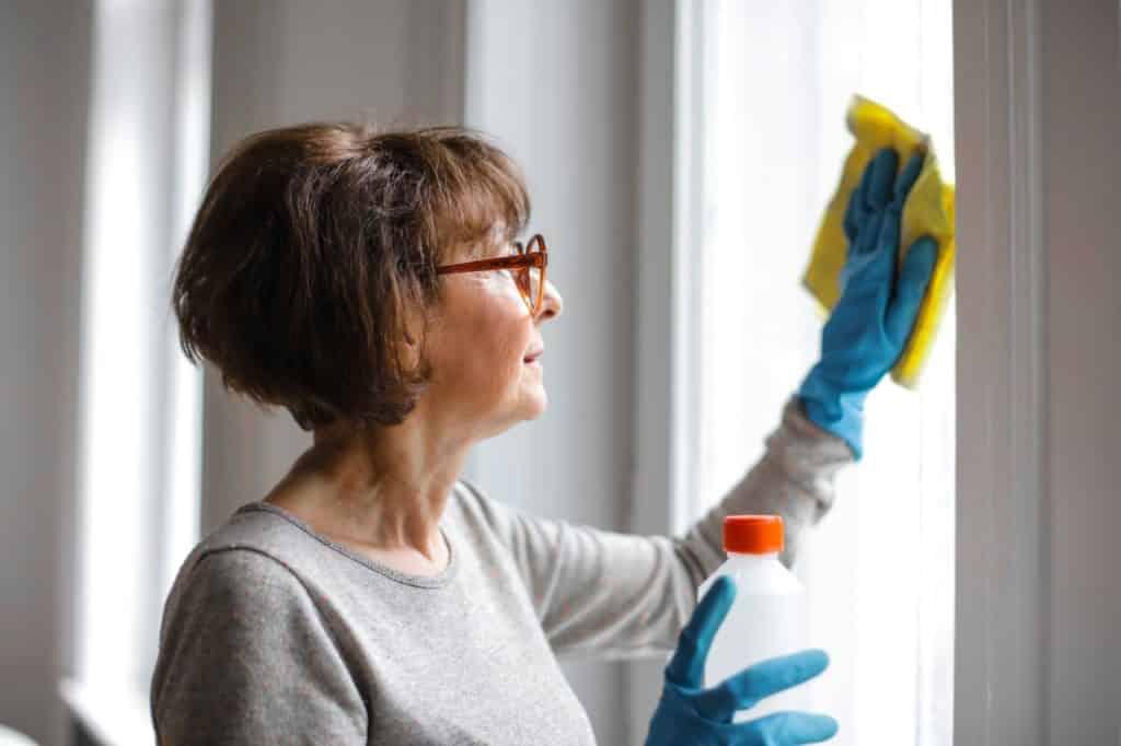 Mulher limpando as janelas de sua casa com luvas de borracha.