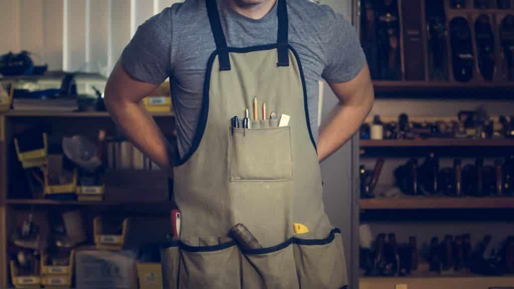 Homem usando um avental com ferramentas de construção em seus bolsosl.
